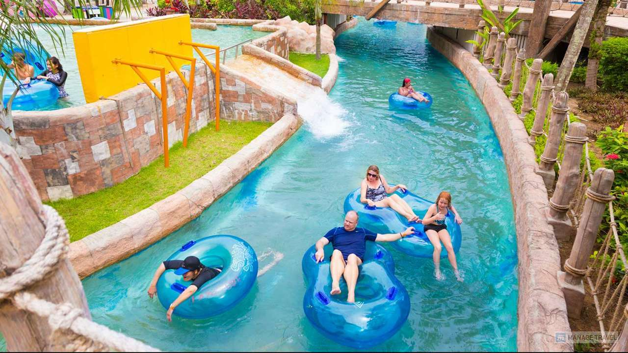 Western family enjoy thier time riding water float tubes in Lazy River at Splash Jungle Water Theme Park in Phuket