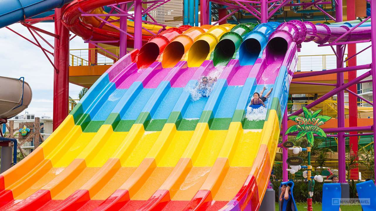 Happy vacationers slide down giant sliders at Splash Jungle Water Theme park in Phuket